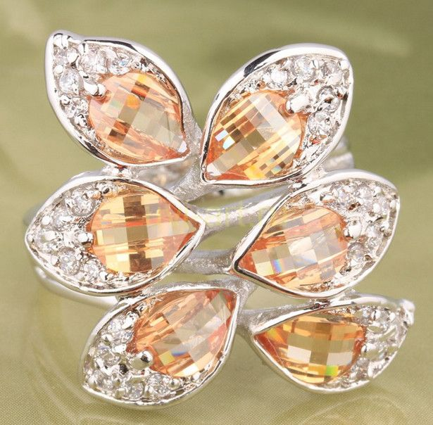 Позолоченное белым золотом кольцо с медовыми цитринами и цирконами