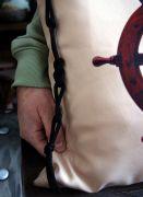 Подушка украшена двумя декоративными шнурами, переплетёнными морскими узлами.